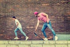 Muchachos del skater por la pared de ladrillo Foto de archivo