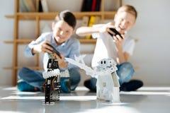 Muchachos emocionados que organizan batallas de guerreros robóticos Fotografía de archivo libre de regalías