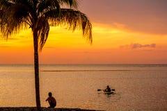 Muchachos en la puesta del sol en la isla caribeña Imagen de archivo libre de regalías
