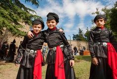 Muchachos en los trajes georgianos de la vieja moda que abrazan como mejores amigos en la muchedumbre de festival de la calle Foto de archivo libre de regalías