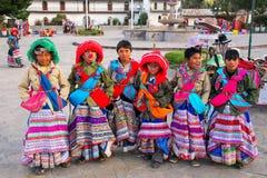 Muchachos en los trajes tradicionales que se colocan en la plaza principal en Yanq Imagenes de archivo