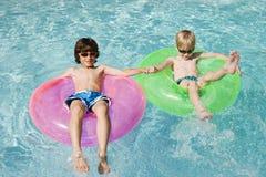 Muchachos en los tubos del flotador en piscina Imagen de archivo