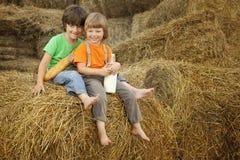 Muchachos en un pajar con pan y leche Fotos de archivo