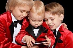 muchachos en un smoking con el móvil Imagen de archivo libre de regalías