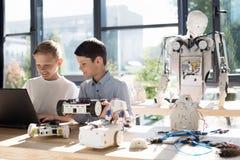 Muchachos encantadores que ponen un vehículo robótico en el ordenador portátil Fotos de archivo libres de regalías