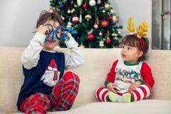 Muchachos felices de los niños que juegan con el árbol de navidad en el fondo Fotografía de archivo libre de regalías