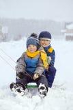 Muchachos felices en el trineo Foto de archivo libre de regalías