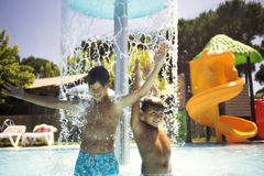 Muchachos felices que juegan con la fuente de agua en la piscina Imagen de archivo libre de regalías