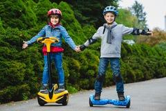 Muchachos felices que montan en hoverboards o gyroscooters al aire libre Imágenes de archivo libres de regalías