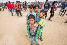 Muchachos felices que se colocan uno por uno en la muchedumbre de gente Fotos de archivo