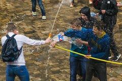 Muchachos felices que vierten el agua en uno a Imagen de archivo