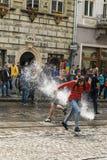 Muchachos felices que vierten el agua en uno a Imagen de archivo libre de regalías