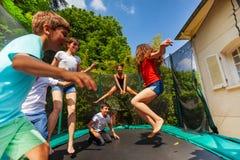 Muchachos felices y muchachas que saltan en el trampolín al aire libre fotos de archivo