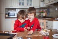 Muchachos, galletas del jengibre que cuecen para la Navidad imagen de archivo