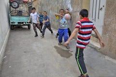 Muchachos iraníes de la calle que juegan a fútbol en la yarda, Shiraz, Irán Fotos de archivo