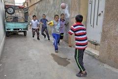 Muchachos iraníes que juegan a fútbol en yarda Fotografía de archivo libre de regalías