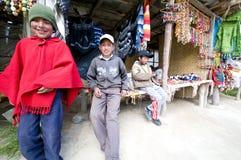 Muchachos jovenes de Ecuador los Andes en la venta de sus artesanías Imagen de archivo libre de regalías