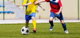 Muchachos jovenes que golpean fútbol del fútbol con el pie en el campo de deportes Te de la juventud Imagen de archivo libre de regalías