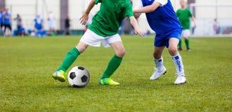 Muchachos jovenes que juegan al juego de fútbol del fútbol en campo de deportes running Imagen de archivo