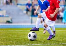 Muchachos jovenes que juegan el partido de fútbol Niños que golpean fútbol con el pie en echada Imágenes de archivo libres de regalías