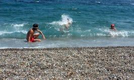 Muchachos jovenes que juegan en el mar Fotografía de archivo