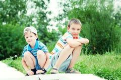 Muchachos jovenes que se sientan junto y que sonríen Fotos de archivo libres de regalías