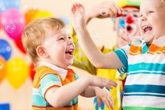 Muchachos juguetones de los cabritos con el payaso en fiesta de cumpleaños Fotos de archivo libres de regalías