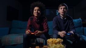 Muchachos lindos que compiten en videojuego en la consola casera almacen de video