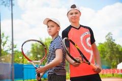 Muchachos lindos que juegan a tenis y que presentan ante el tribunal al aire libre foto de archivo