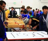 Muchachos que adaptan encima de su robot en el RoboGames Foto de archivo libre de regalías