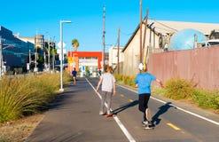 Muchachos que andan en monopatín en la trayectoria de la bici del metro de Los Ángeles Fotografía de archivo