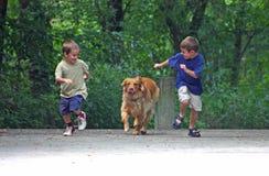 Muchachos que compiten con el perro Imagen de archivo libre de regalías