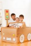 Muchachos que conducen al papá en el coche del juguete hecho de la caja de cartón Foto de archivo libre de regalías