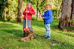 Muchachos que destruyen el tronco de madera con el martillo de trineo en el parque Fotos de archivo
