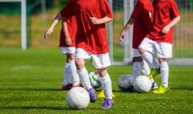 Muchachos que entrenan a fútbol en el campo de fútbol Entrenamiento del fútbol de los niños Imagen de archivo