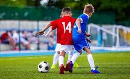 Muchachos que golpean el balón de fútbol con el pie en echada de la hierba Futbolistas de los niños Fotografía de archivo