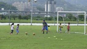 Muchachos que golpean fútbol con el pie en el campo de deportes Fotografía de archivo libre de regalías