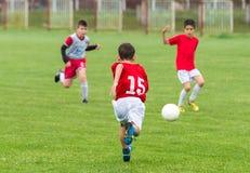 Muchachos que golpean la bola con el pie Foto de archivo libre de regalías