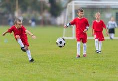 Muchachos que golpean la bola con el pie Imagenes de archivo