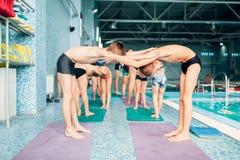 Muchachos que hacen ejercicios juguetones en pares cerca de piscina Imagen de archivo