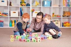 Muchachos que juegan al juego con los bloques de los cabritos con la madre Imagenes de archivo