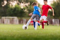 Muchachos que juegan al juego de fútbol del fútbol en campo de deportes Imágenes de archivo libres de regalías