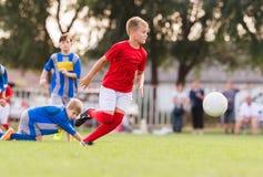 Muchachos que juegan al juego de fútbol del fútbol en campo de deportes Imagen de archivo libre de regalías