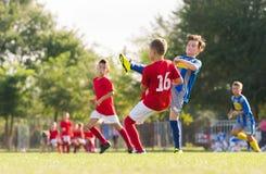 Muchachos que juegan al juego de fútbol del fútbol en campo de deportes Fotos de archivo libres de regalías