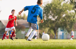 Muchachos que juegan al juego de fútbol del fútbol en campo de deportes Foto de archivo
