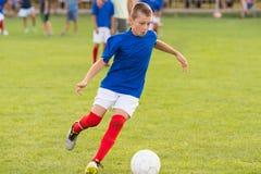 Muchachos que juegan al juego de fútbol del fútbol en campo de deportes Foto de archivo libre de regalías