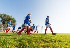 Muchachos que juegan al juego de fútbol del fútbol en campo de deportes Fotografía de archivo libre de regalías