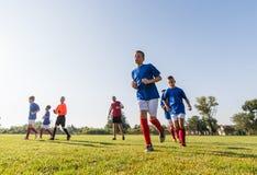Muchachos que juegan al juego de fútbol del fútbol en campo de deportes Imagen de archivo