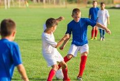 Muchachos que juegan al juego de fútbol del fútbol en campo de deportes Imagenes de archivo