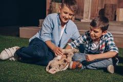 Muchachos que juegan con el perrito lindo de Labrador junto Imagen de archivo libre de regalías